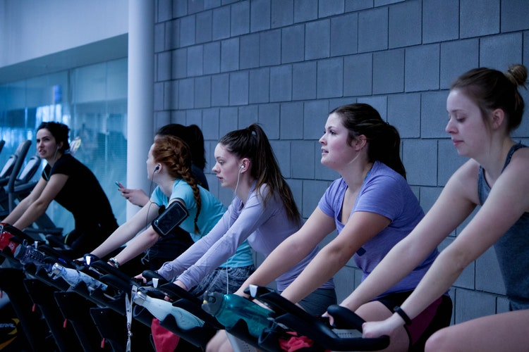group of women doing exercise in a Stationary Bike